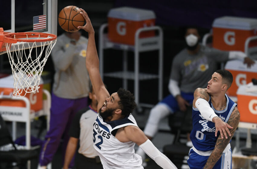 LOS ANGELES, CALIFORNIA - MARCH 16: Karl-Anthony Towns #32 of the Minnesota Timberwolves dunks past Kyle Kuzma #0 of the Los Angeles Lakers during a 137-121 Lakers win at Staples Center on March 16, 2021 in Los Angeles, California. (Photo by Harry How/Getty Images) NOTE TO USER: User expressly acknowledges and agrees that, by downloading and or using this photograph, User is consenting to the terms and conditions of the Getty Images License Agreement.