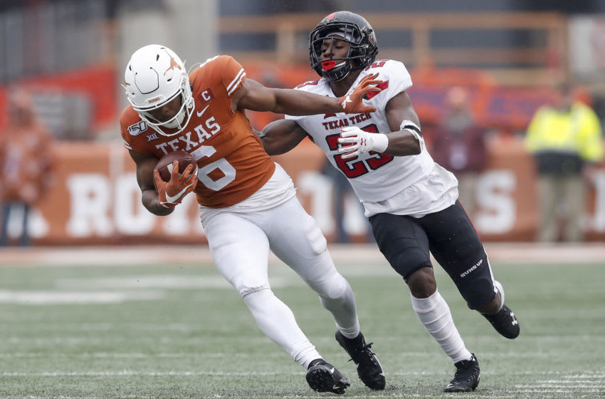 AUSTIN, TX - NOVEMBER 29: Devin Duvernay #6 of the Texas Longhorns attempts to avoid a tackle by Damarcus Fields #23 of the Texas Tech Red Raiders in the second half at Darrell K Royal-Texas Memorial Stadium on November 29, 2019 in Austin, Texas. (Photo by Tim Warner/Getty Images)