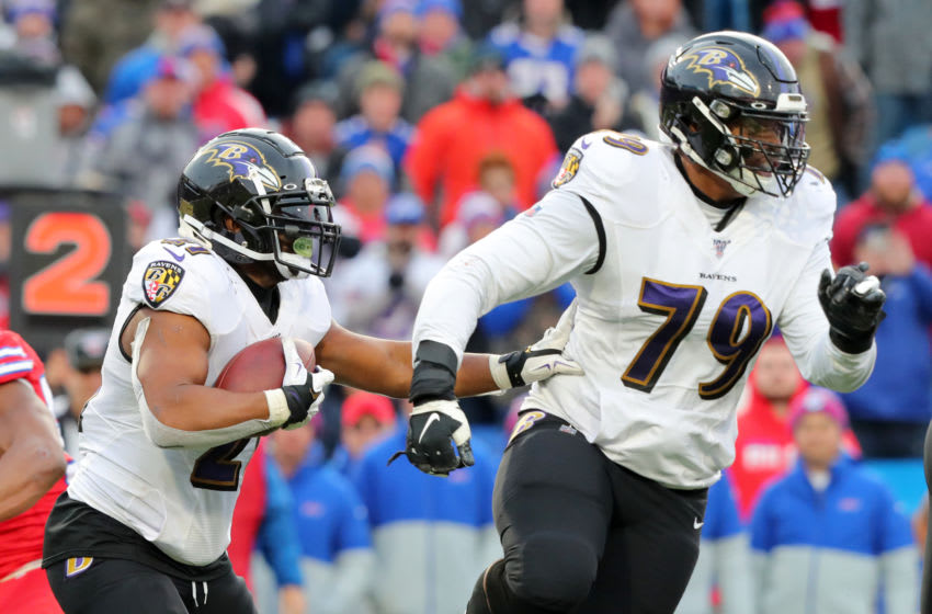 ORCHARD PARK, NY - DECEMBER 8: Ronnie Stanley #79 of the Baltimore Ravens looks to make a block for Mark Ingram #21 as he runs the ball during the second half against the Buffalo Bills at New Era Field on December 8, 2019 in Orchard Park, New York. Baltimore beats Buffalo 24 to 17. (Photo by Timothy T Ludwig/Getty Images)