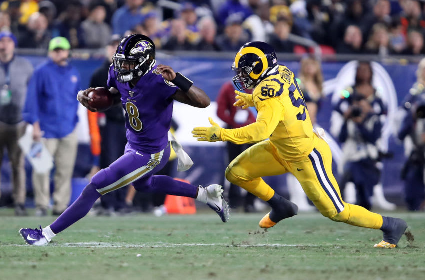 LOS ANGELES, CALIFORNIA - NOVEMBER 25: Lamar Jackson #8 of the Baltimore Ravens eludes the defense of Samson Ebukam #50 of the Los Angeles Rams during the second half of a game at Los Angeles Memorial Coliseum on November 25, 2019 in Los Angeles, California. (Photo by Sean M. Haffey/Getty Images)