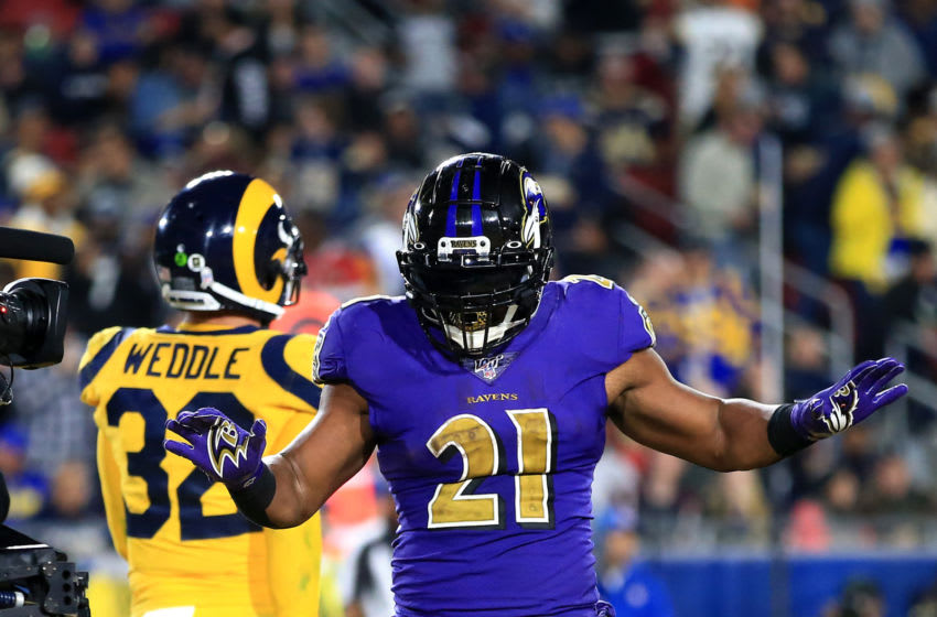 LOS ANGELES, CALIFORNIA - NOVEMBER 25: Mark Ingram #21 of the Baltimore Ravens dances after scoring on a rushing touchdown as Eric Weddle #32 of the Los Angeles Rams looks during the second half of a game at Los Angeles Memorial Coliseum on November 25, 2019 in Los Angeles, California. (Photo by Sean M. Haffey/Getty Images)