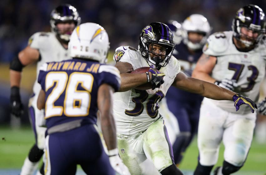 CARSON, CA - DECEMBER 22: Casey Hayward #26 of the Los Angeles Chargers defends as Kenneth Dixon #30 of the Baltimore Ravens runs the ball during the first half of a game at StubHub Center on December 22, 2018 in Carson, California. (Photo by Sean M. Haffey/Getty Images)
