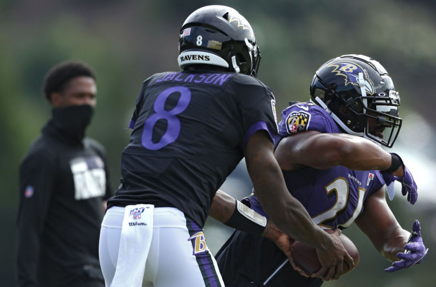 OWINGS MILLS, MARYLAND - AUGUST 17: Quarterback Lamar Jackson #8 of the Baltimore Ravens hands off to running back Mark Ingram II #21 of the Baltimore Ravens during the Baltimore Ravens Training Camp at Under Armour Performance Center Baltimore Ravens on August 17, 2020 in Owings Mills, Maryland. (Photo by Patrick Smith/Getty Images)