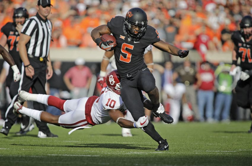 STILLWATER, OK - NOVEMBER 04: Running back Justice Hill #5 of the Oklahoma State Cowboys is hit by defensive back Steven Parker #10 of the Oklahoma Sooners at Boone Pickens Stadium on November 4, 2017 in Stillwater, Oklahoma. (Photo by Brett Deering/Getty Images)