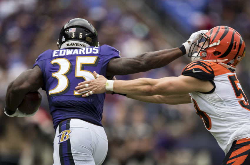 Gus Edwards #35 of the Baltimore Ravens fights off Nick Vigil #59 of the Cincinnati Bengals (Photo by Scott Taetsch/Getty Images)