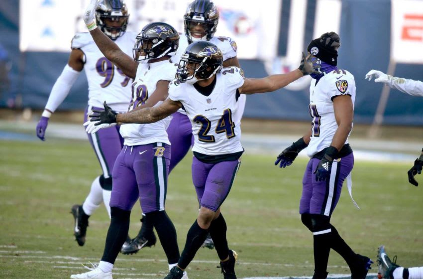 Baltimore Ravens cornerback Marcus Peters (24) and his teammates stomp on the Titans logo after Peters picked up an interception to seal their win over the Tennessee Titans in Nashville on January 10, 2021. Titans Ravens 185