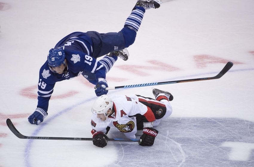 Oct 10, 2015; Toronto, Ontario, CAN; TToronto Maple Leafs left wing Leafs Joffrey Lupul (19) falls over Ottawa Senators center Kyle Turris (7) in the third period at Air Canada Centre. Senators beat Leafs 5 - 4. Mandatory Credit: Peter Llewellyn-USA TODAY Sports