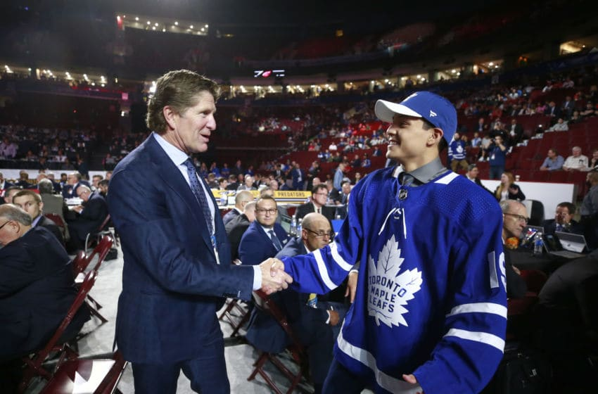 VANCOUVER, BRITISH COLUMBIA - JUNE 22: Nicholas Robertson, 53rd overall pick of the Toronto Maple Leafs, is greeted by head coach Mike Babcock of the Toronto Maples at the team draft table during Rounds 2-7 of the 2019 NHL Draft at Rogers Arena on June 22, 2019 in Vancouver, Canada. (Photo by Jeff Vinnick/NHLI via Getty Images)