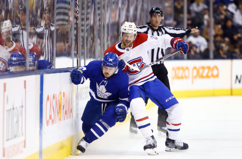 TORONTO, ON - OCTOBER 05: Jeff Petry #26 of the Montreal Canadiens checks Auston Matthews #34 of the Toronto Maple Leafs into the boards during an NHL game at Scotiabank Arena on October 5, 2019 in Toronto, Canada. (Photo by Vaughn Ridley/Getty Images)