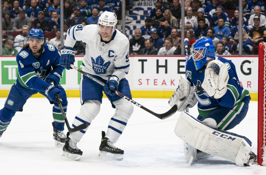 VANCOUVER, BC - DECEMBER 10: Christopher Tanev #8 of the Vancouver Canucks and John Tavares #91 of the Toronto Maple Leafs watches the puck hit goalie Jacob Markstrom #25 of the Vancouver Canucks during NHL action at Rogers Arena on December 10, 2019 in Vancouver, Canada. (Photo by Rich Lam/Getty Images)