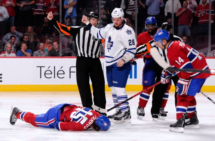 Colton Orr #28 of the Toronto Maple Leafs calls for the Montreal Canadiens trainers to tend to George Parros #15. 2013 (Photo by Richard Wolowicz/Getty Images)