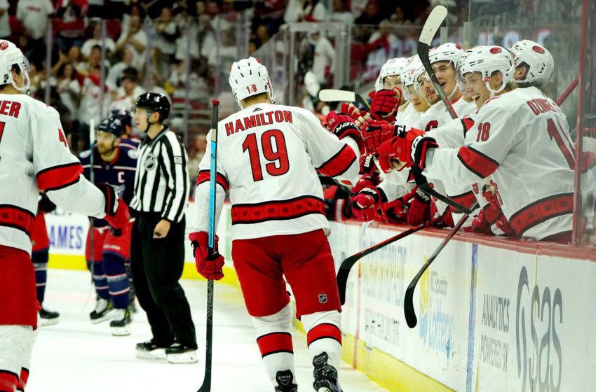RALEIGH, NC - OCTOBER 12: Dougie Hamilton #19 of the Carolina Hurricanes skates to the bench and celebrates with teammates after scoring a goal against the Columbus Blue Jackets during an NHL game on October 12, 2019 at PNC Arena in Raleigh North Carolina. (Photo by Gregg Forwerck/NHLI via Getty Images)