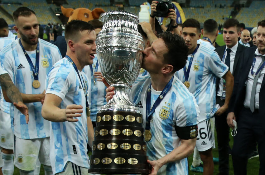 Lionel Messi of Argentina kisses the trophy as he celebrates with teammates after winning the final of Copa America. (Photo by Alexandre Schneider/Getty Images)