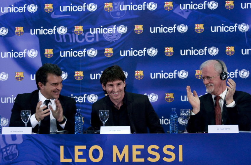 Barcelona's Argentinian forward Lionel Messi (C) aknowledges applause from Barcelona FC President Joan Laporta (L) and UN Children's Fund (UNICEF) Regional Director for the UNICEF Regional Office for Geneva, Philip O'Brien (R) (Photo credit JOSEP LAGO/AFP via Getty Images)