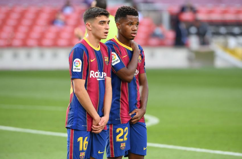 Barcelona's Spanish midfielder Pedri (L) and Barcelona's Spanish midfielder Ansu Fati attend the Spanish League football match between Barcelona and Real Madrid at the Camp Nou stadium in Barcelona on October 24, 2020. (Photo by LLUIS GENE / AFP) (Photo by LLUIS GENE/AFP via Getty Images)