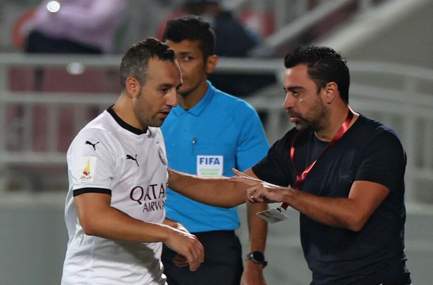 Sadd's coach Xavi Hernandez (R) speaks to Santi Cazorla. (Photo by KARIM JAAFAR / AFP) (Photo by KARIM JAAFAR/AFP via Getty Images)