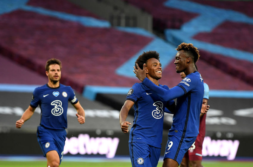 LONDON, ENGLAND - JULY 01: Willian of Chelsea celebrates with teammate Tammy Abraham after scoring his team's first goal from a penalty during the Premier League match between West Ham United and Chelsea FC at London Stadium on July 01, 2020 in London, England. Football Stadiums around Europe remain empty due to the Coronavirus Pandemic as Government social distancing laws prohibit fans inside venues resulting in all fixtures being played behind closed doors. (Photo by Michael Regan/Getty Images)