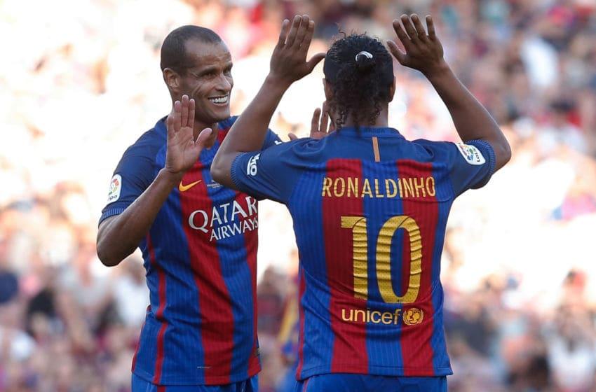 Former Barcelona's Brazilian forward Ronaldinho (R) and former Barcelona's Brazilian midfielder Rivaldo. (Photo credit PAU BARRENA/AFP via Getty Images)