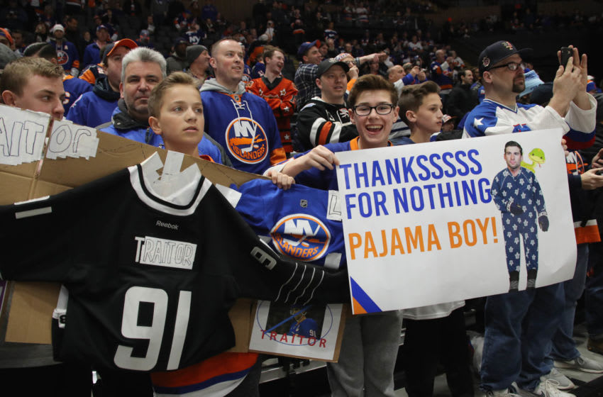 UNIONDALE, NEW YORK - FEBRUARY 28: Fans hold signs regarding John Tavares #91 of the Toronto Maple Leafs and his signing with that team this past summer at NYCB Live's Nassau Coliseum on February 28, 2019 in Uniondale City. (Photo by Bruce Bennett/Getty Images)
