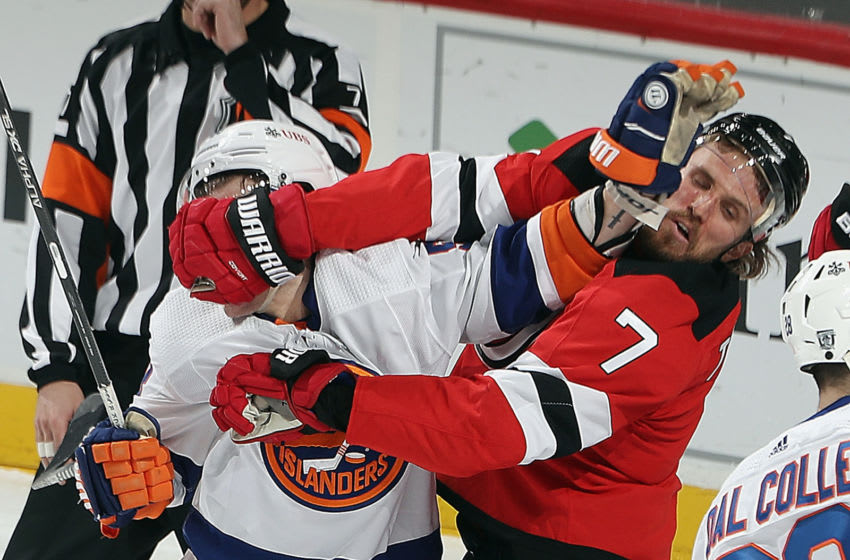 NEWARK, NEW JERSEY - JANUARY 24: Casey Cizikas #53 of the New York Islanders and Matt Tennyson #7 of the New Jersey Devils get the gloves up during the third period at the Prudential Center on January 24, 2021 in Newark, New Jersey. (Photo by Bruce Bennett/Getty Images)