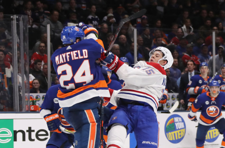 UNIONDALE, NEW YORK - MARCH 14: Scott Mayfield #24 of the New York Islanders checks Jesperi Kotkaniemi #15 of the Montreal Canadiens during the third period at NYCB Live's Nassau Coliseum on March 14, 2019 in Uniondale, New York. The Islanders defeated the Canadiens 2-1. (Photo by Bruce Bennett/Getty Images)