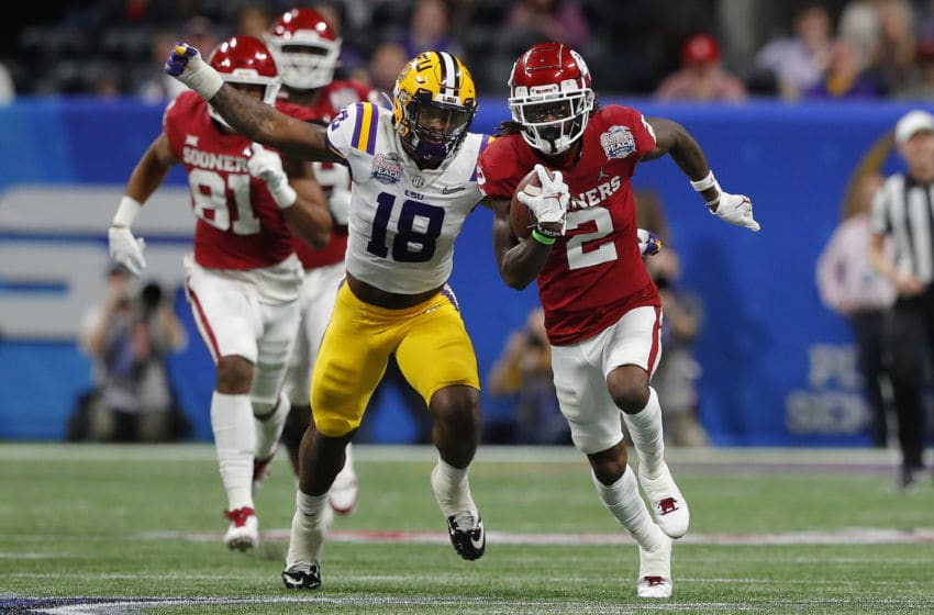 ATLANTA, GEORGIA - DECEMBER 28: Wide receiver CeeDee Lamb #2 of the Oklahoma Sooners carries the ball against linebacker K'Lavon Chaisson #18 of the LSU Tigers during the Chick-fil-A Peach Bowl at Mercedes-Benz Stadium on December 28, 2019 in Atlanta, Georgia. (Photo by Kevin C. Cox/Getty Images)