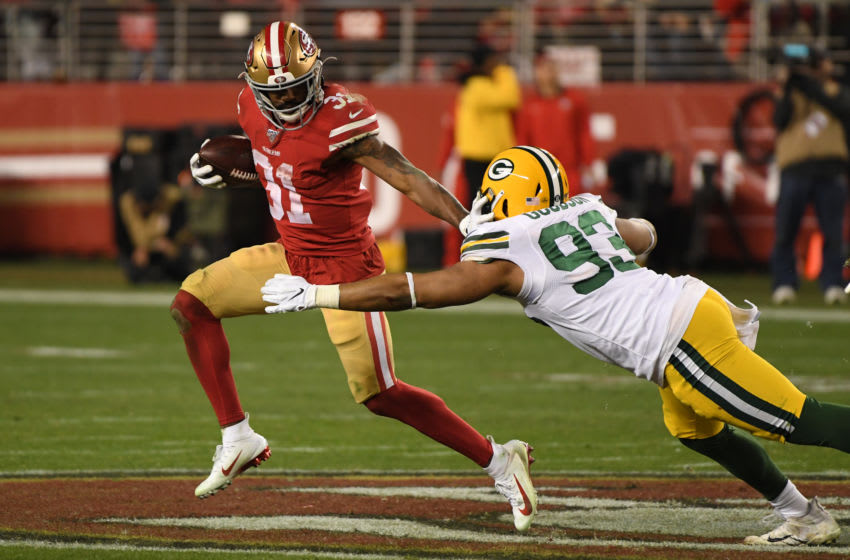 SANTA CLARA, CALIFORNIA - JANUARY 19: Raheem Mostert #31 of the San Francisco 49ers stiff arms B.J. Goodson #93 of the Green Bay Packers during the second half of the NFC Championship game at Levi's Stadium on January 19, 2020 in Santa Clara, California. (Photo by Harry How/Getty Images)