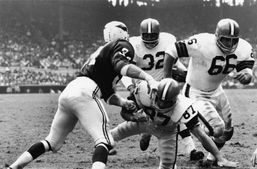 American football player Jim Brown, running back for the Cleveland Browns, runs the ball behind three blockers in action against the St. Louis Cardinals during a home game at Cleveland Municipal Stadium, Cleveland, Ohio, 1960s. (Photo by Robert Riger/Getty Images)