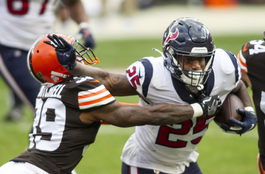 Nov 15, 2020; Cleveland, Ohio, USA; Houston Texans running back Duke Johnson (25) stiff arms Cleveland Browns cornerback Terrance Mitchell (39) as he moves in for the tackle during the second quarter at FirstEnergy Stadium. Mandatory Credit: Scott Galvin-USA TODAY Sports