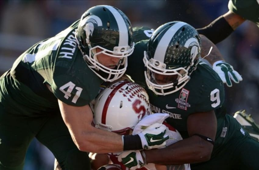 Jan 1, 2014; Pasadena, CA, USA; Michigan State Spartans linebacker Kyler Elsworth (41) and safety Isiah Lewis (9) tackle Stanford Cardinal running back Tyler Gaffney (25) in the 100th Rose Bowl. Mandatory Credit: Kirby Lee-USA TODAY Sports
