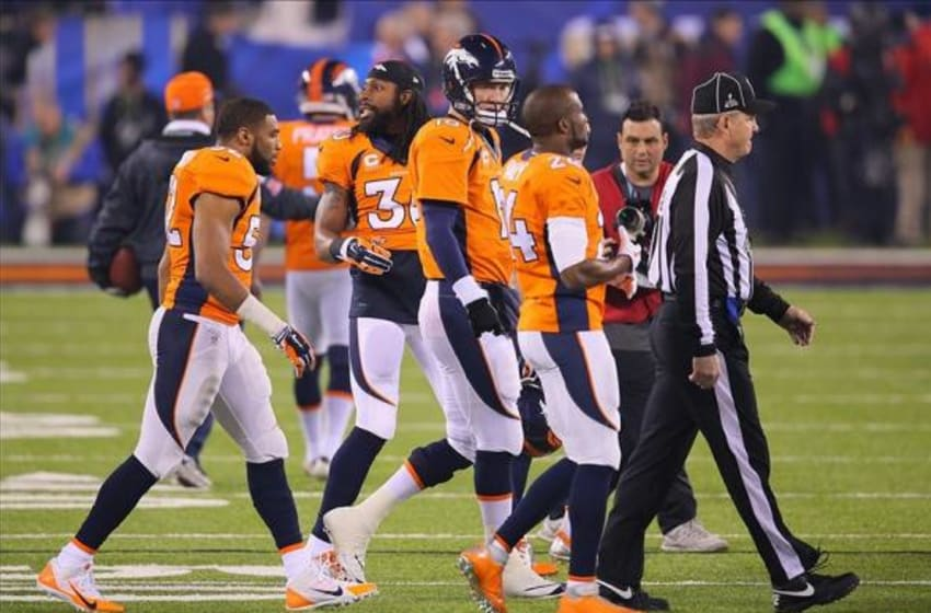 Feb 2, 2014; East Rutherford, NJ, USA; Denver Broncos quarterback Peyton Manning (18) cornerback Champ Bailey (24) strong safety David Bruton (30) and cornerback Chris Harris (25) walk to midfield for the coin toss before Super Bowl XLVIII at MetLife Stadium. Mandatory Credit: Adam Hunger-USA TODAY Sports