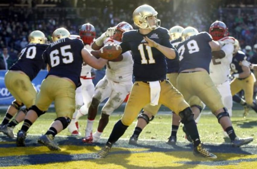 Dec 28, 2013; Bronx, NY, USA; Notre Dame Fighting Irish quarterback Tommy Rees (11) throws a pass in the first quarter against the Rutgers Scarlet Knights during the Pinstripe Bowl at Yankee Stadium. Mandatory Credit: Andrew Mills/THE STAR-LEDGER via USA TODAY Sports