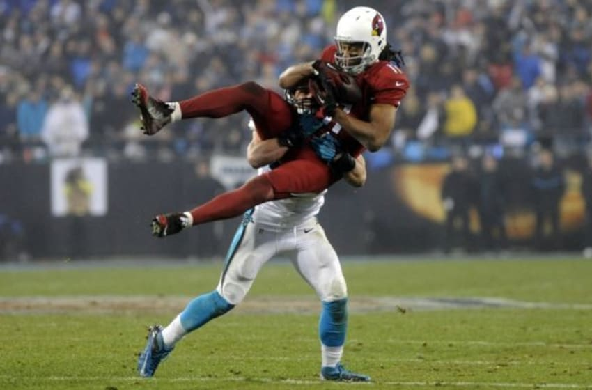 Jan 3, 2015; Charlotte, NC, USA; Arizona Cardinals wide receiver Larry Fitzgerald (11) catches a pass over Carolina Panthers middle linebacker Luke Kuechly (59) during the fourth quarter in the 2014 NFC Wild Card playoff football game at Bank of America Stadium. Mandatory Credit: Sam Sharpe-USA TODAY Sports