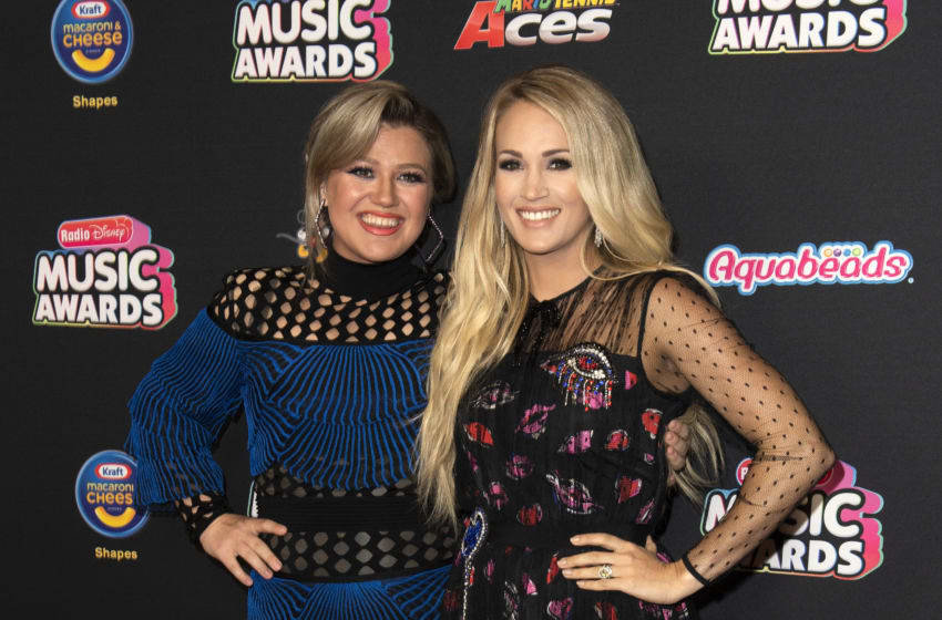 Singers/Songwriters Kelly Clarkson (L) and Carrie Underwood attend the 2018 Radio Disney Music Awards at Loews Hollywood Hotel on June 12, 2018 in Hollywood, California. (Photo by VALERIE MACON / AFP) (Photo credit should read VALERIE MACON/AFP/Getty Images)