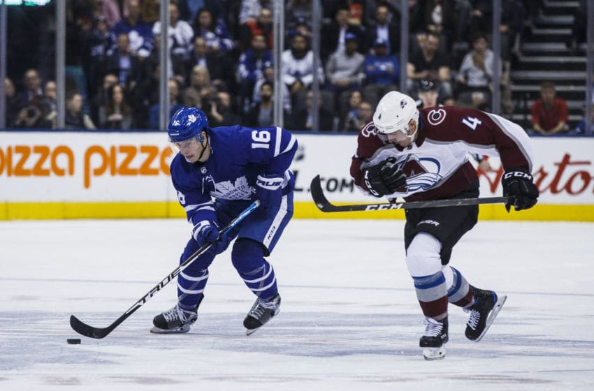 TORONTO, ON - JANUARY 14: Mitch Marner #16 of the Toronto Maple Leafs plays the puck against Tyson Barrie #4 of the Colorado Avalanche during the second period at the Scotiabank Arena on January 14, 2019 in Toronto, Ontario, Canada. (Photo by Mark Blinch/NHLI via Getty Images)