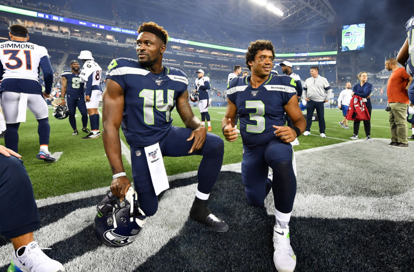 SEATTLE, WASHINGTON - AUGUST 08: D.K. Metcalf #14 and Russell Wilson #3 of the Seattle Seahawks take a knee after the preseason game victory over the Denver Broncos at CenturyLink Field on August 08, 2019 in Seattle, Washington. (Photo by Alika Jenner/Getty Images)