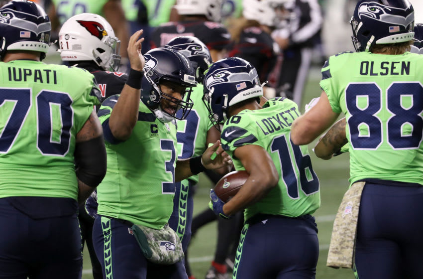 SEATTLE, WASHINGTON - NOVEMBER 19: Russell Wilson #3 congratulates Tyler Lockett #16 of the Seattle Seahawks reacts after he a caught a pass for a touchdown in front of Patrick Peterson #21 of the Arizona Cardinals at Lumen Field on November 19, 2020 in Seattle, Washington. (Photo by Abbie Parr/Getty Images)