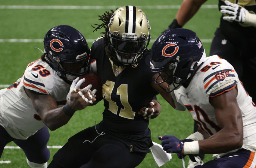 NEW ORLEANS, LOUISIANA - JANUARY 10: Alvin Kamara #41 of the New Orleans Saints runs the ball against Danny Trevathan #59 and Barkevious Mingo #50 of the Chicago Bears during the fourth quarter in the NFC Wild Card Playoff game at Mercedes Benz Superdome on January 10, 2021 in New Orleans, Louisiana. (Photo by Chris Graythen/Getty Images)