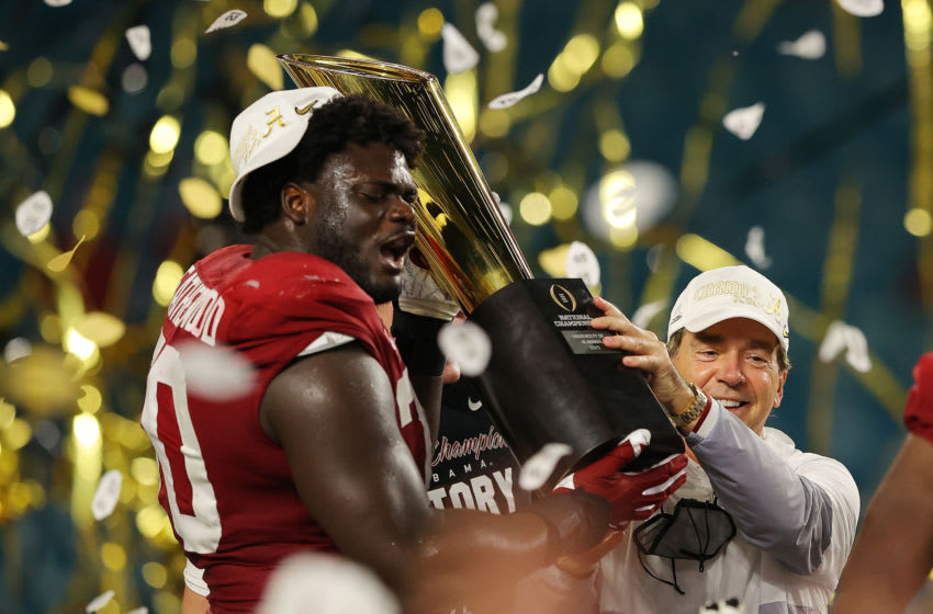 MIAMI GARDENS, FLORIDA - JANUARY 11: Alex Leatherwood #70 of the Alabama Crimson Tide holds the trophy alongside head coach Nick Saban following the College Football Playoff National Championship game win over the Ohio State Buckeyes at Hard Rock Stadium on January 11, 2021 in Miami Gardens, Florida. (Photo by Kevin C. Cox/Getty Images)
