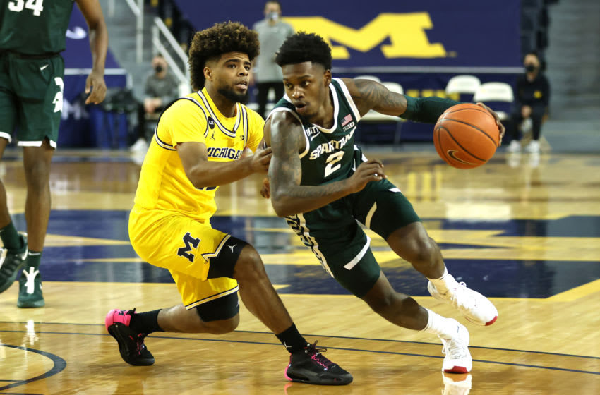 ANN ARBOR, MICHIGAN - MARCH 04: Rocket Watts #2 of the Michigan State Spartans drives around Mike Smith #12 of the Michigan Wolverines during the first half at Crisler Arena on March 04, 2021 in Ann Arbor, Michigan. (Photo by Gregory Shamus/Getty Images)