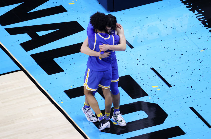 INDIANAPOLIS, INDIANA - APRIL 03: Jaime Jaquez Jr. #4 and Johnny Juzang #3 of the UCLA Bruins hug after being defeated by the Gonzaga Bulldogs 93-90 in overtime during the 2021 NCAA Final Four semifinal at Lucas Oil Stadium on April 03, 2021 in Indianapolis, Indiana. (Photo by Andy Lyons/Getty Images)