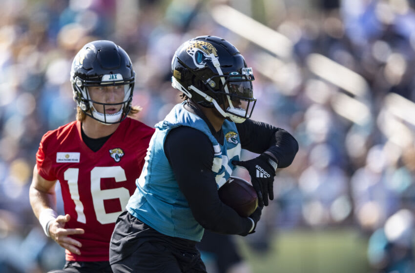 Trevor Lawrence #16 of the Jacksonville Jaguars hands the ball off to James Robinson #30 during Training Camp at TIAA Bank Field on July 29, 2021 in Jacksonville, Florida. (Photo by James Gilbert/Getty Images)