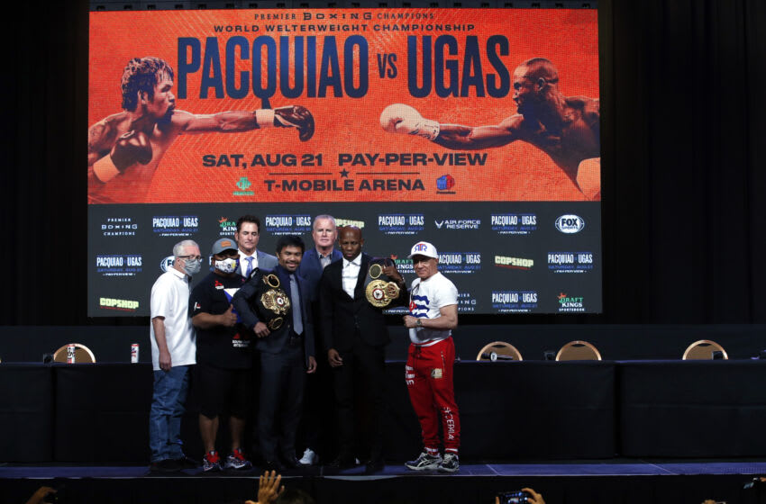 LAS VEGAS, NEVADA - AUGUST 18: Manny Pacquiao (L) and WBA welterweight champion Yordenis Ugas pose with trainers and members of their teams during a news conference at MGM Grand Garden Arena on August 18, 2021 in Las Vegas, Nevada. Pacquiao will challenge Ugas for his title at T-Mobile Arena on August 21 in Las Vegas. (Photo by Steve Marcus/Getty Images)