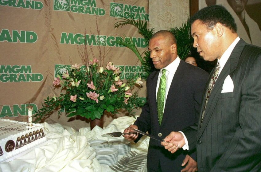 Mohammad Ali(R) and Mike Tyson(L) cut a piece of birthday cake during celebrations to mark Ali's 57th birthday at in Las Vegas 17 January. Tyson defeated Francois Botha of South Africa 16 January in the fifth round of their heavyweight fight in Las Vegas. AFP PHOTO John Gurzinski (Photo credit should read JOHN GURZINSKI/AFP via Getty Images)