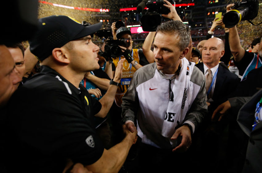 ARLINGTON, TX - JANUARY 12: Head Coach Urban Meyer (R) of the Ohio State Buckeyes shakes hands with Head coach Mark Helfrich (L) of the Oregon Ducks after the College Football Playoff National Championship Game at AT&T Stadium on January 12, 2015 in Arlington, Texas. The Ohio State Buckeyes defeated the Oregon Ducks 42 to 20. (Photo by Ronald Martinez/Getty Images)