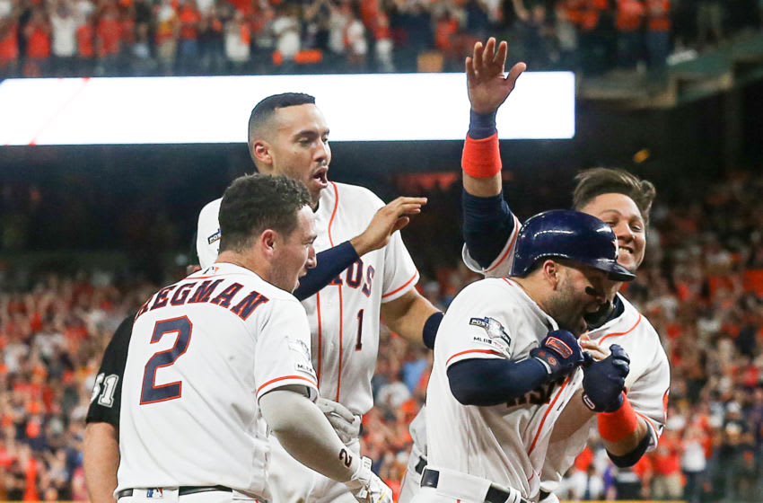 HOUSTON, TEXAS - OCTOBER 19: Jose Altuve #27 of the Houston Astros is mobbed by Alex Bregman #2, Carlos Correa #1 and Yuli Gurriel #10 as he approaches home plate after hitting a walk-off home run against the New York Yankees to winGame 6 of the American League Championship Series at Minute Maid Park on October 19, 2019 in Houston, Texas. (Photo by Bob Levey/Getty Images)