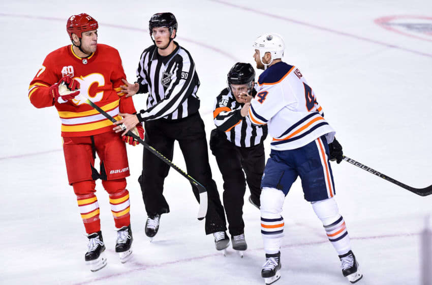 CALGARY, AB - JANUARY 11: Officials insert themselves between Calgary Flames Left Wing Milan Lucic (17) and Edmonton Oilers Right Wing Zack Kassian (44) during the third period of an NHL game where the Calgary Flames hosted the Edmonton Oilers on January 11, 2020, at the Scotiabank Saddledome in Calgary, AB. (Photo by Brett Holmes/Icon Sportswire via Getty Images)