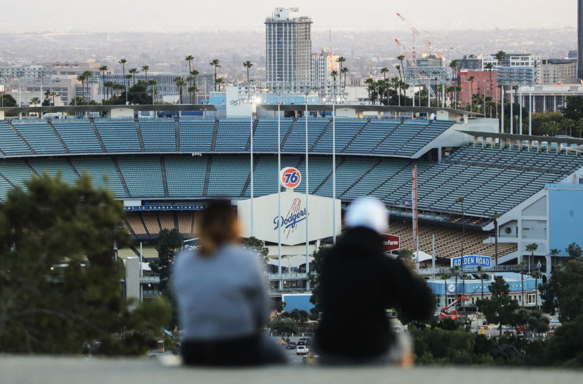 LOS ANGELES, CALIFORNIA - MARCH 26: People sit on a hill overlooking Dodger Stadium on what was supposed to be Major League Baseball's opening day, now postponed due to the coronavirus, on March 26, 2020 in Los Angeles, California. The Los Angeles Dodgers were slated to play against the San Francisco Giants at the stadium today. Major League Baseball Commissioner Rob Manfred recently said the league is