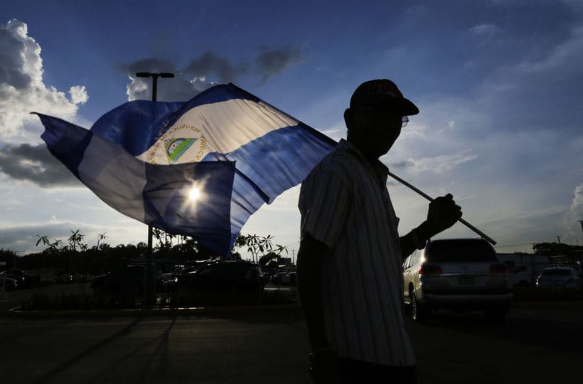 A fan of the National Baseball Team of Nicaragua walks with a flag of Nicaragua before the friendly game of the National Baseball Team of Nicaragua against the National Baseball Team of Taiwan in the Stadium