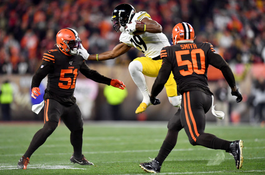 CLEVELAND, OHIO - NOVEMBER 14: Wide receiver JuJu Smith-Schuster #19 of the Pittsburgh Steelers carries the ball against the defnse of Mack Wilson #51 and defensive end Chris Smith #50 of the Cleveland Browns ns at FirstEnergy Stadium on November 14, 2019 in Cleveland, Ohio. (Photo by Jamie Sabau/Getty Images)